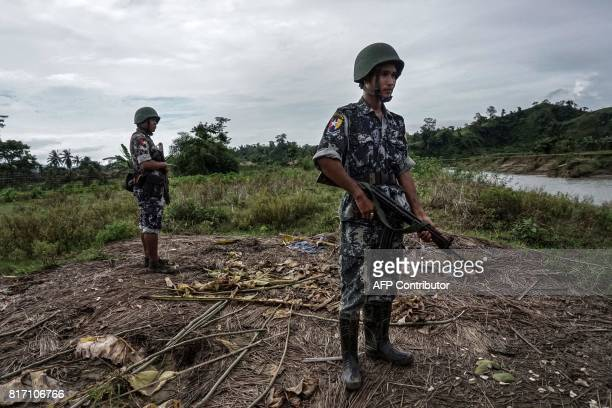 This photo taken on July 14 2017 shows border police standing guard at Tinmay village Buthidaung township in Myanmar's northern Rakhine state Hemmed...
