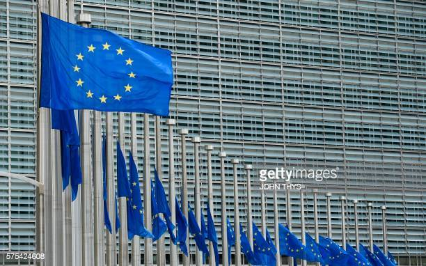 This photo taken on July 15, 2016 shows European Union flags flying at half-mast in front of the European Commission building in Brussels on July 15...