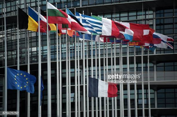 This photo taken on July 15, 2016 shows the French and European Union flags flying at half-mast in front of the European Parliament building in...