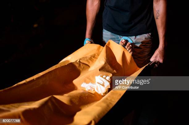 This photo taken on July 15 2017 shows a coroner a stretcher with the body of an alleged drug dealer murdered by unidentified assaillants in Manila...