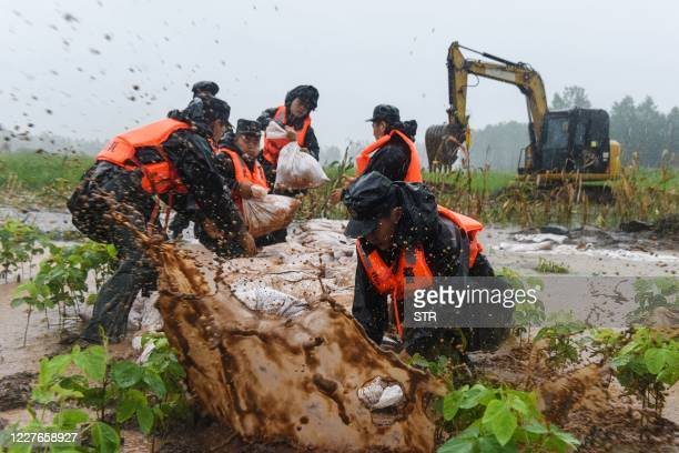 This photo taken on July 15, 2020 shows China's paramilitary police officers placing sandbags on a levee in the rain near the Yangtze River in...