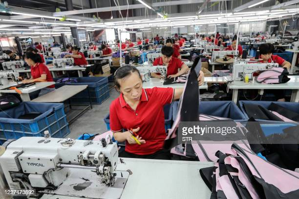 This photo taken on July 15, 2020 shows workers producing bags that will be exported at a textile factory in Huaibei in China's eastern Anhui...