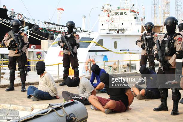 This photo taken on July 16 2017 shows Indonesian policemen standing guard after the arrest of five Taiwanese crew members from a boat named the...