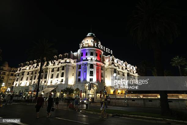 This photo taken on July 17 2016 on the Promenade des Anglais in Nice shows the Hotel Negresco illuminated in the colours of France's flag in tribute...