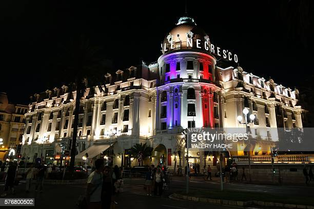 TOPSHOT This photo taken on July 17 2016 on the Promenade des Anglais in Nice shows the Hotel Negresco illuminated in the colours of France's flag in...