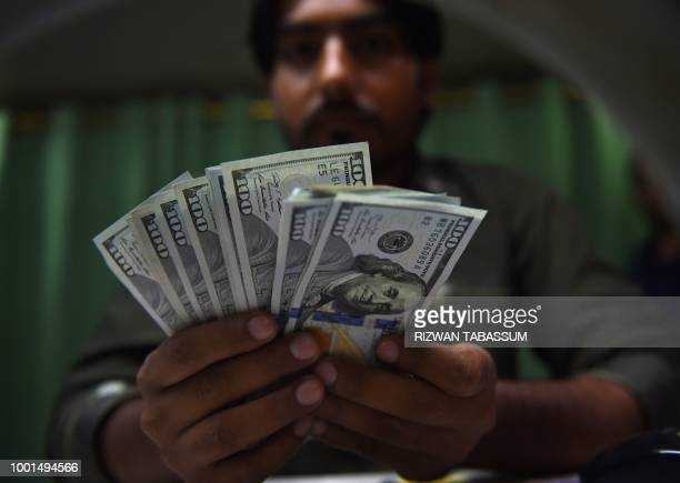 This photo taken on July 17 2018 shows a Pakistani currency dealer counting US dollars banknotes at a currency exchange shop in Karachi Pakistan's...