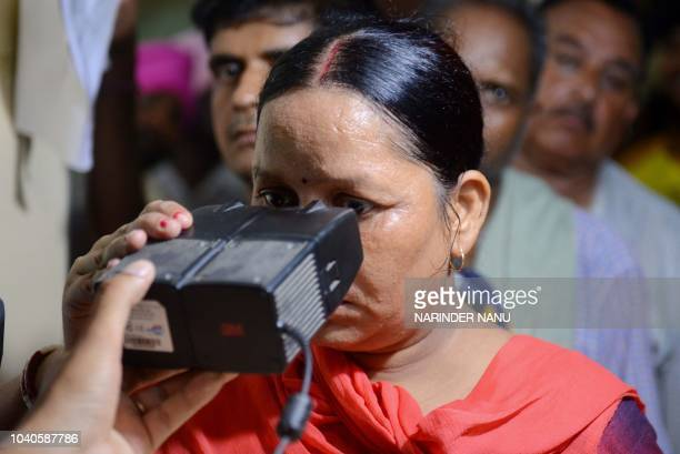 This photo taken on July 17 2018 shows an Indian woman looking through an optical biometric reader that which scans an individual's iris patterns...
