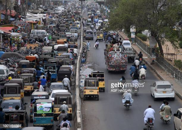 This photo taken on July 17 2018 shows Pakistani commuters driving along a street in Karachi Conservative Pakistan with its limited family planning...