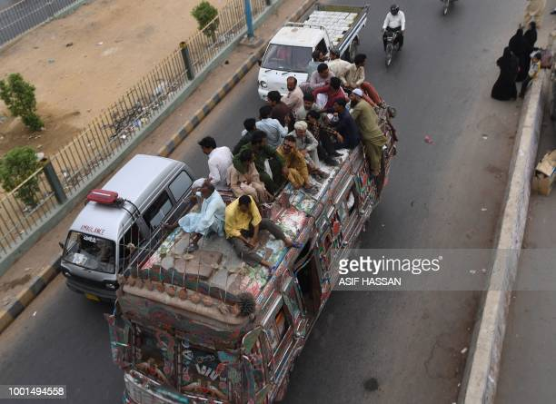 This photo taken on July 17 2018 shows Pakistani residents travelling on an overloaded passenger bus in Karachi Conservative Pakistan with its...