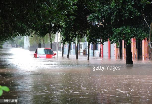 This photo taken on July 18, 2019 shows a flooded street in Dazhou City, in China's southwest Sichuan Province. - Heavy rainfall from July 16-18...