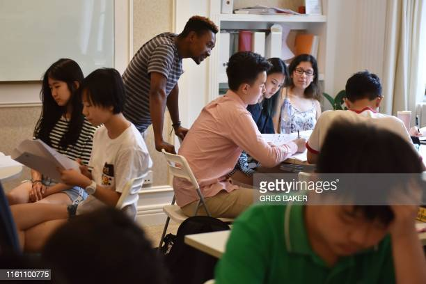 This photo taken on July 19 2019 shows college counsellor Bongani Ndlovu speaking with students during a class at Elite Scholars China a boutique...