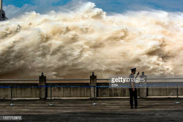 This photo taken on July 19, 2020 shows a security guard looking at his smartphone while water is released from the Three Gorges Dam, a gigantic...