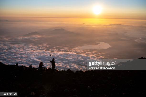This photo taken on July 19, 2021 shows people watching the sunrise from the summit of Mount Fuji, some 70 kilometres west of the capital Tokyo. -...