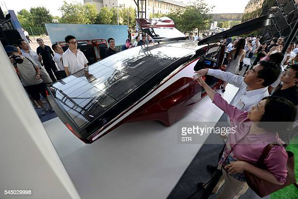 This photo taken on July 2 2016 shows people looking at a Hanergy solarpowered car during a launch event in Beijing Thinfilm power giant Hanergy...