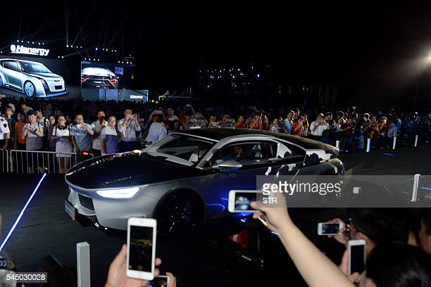 This photo taken on July 2 2016 shows people taking photographs of a Hanergy solarpowered car during a launch event in Beijing Thinfilm power giant...