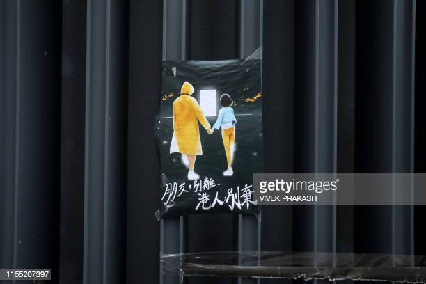 TOPSHOT This photo taken on July 2 2019 shows a poster that reads my friend don't leaveHong Kongers don't give up related to protests against the...