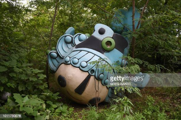 TOPSHOT This photo taken on July 20 2018 shows Beibei one of five mascots for the 2008 Beijing Olympic Games lying amongst trees behind an abandoned...