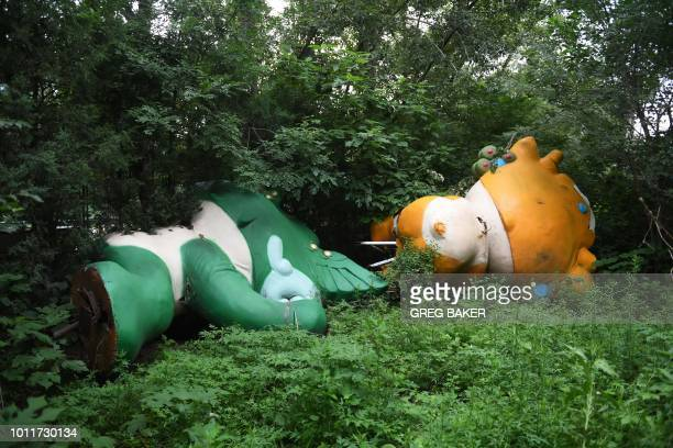 This photo taken on July 20, 2018 shows Nini and Yingying, two of the five mascots for the 2008 Beijing Olympic Games, lying among trees behind an...