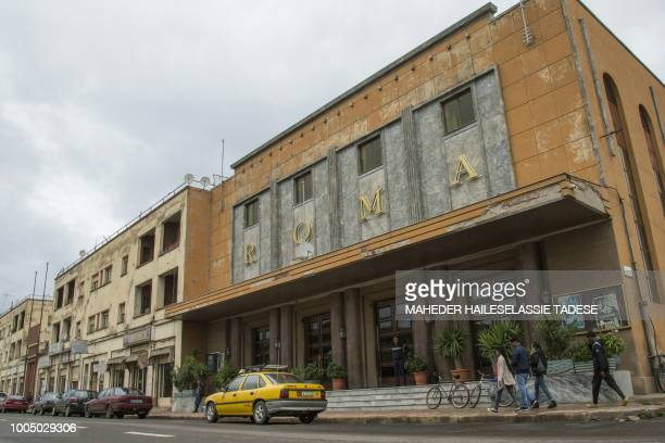 This photo taken on July 20, 2018 shows people walking in front of an art-deco cinema Roma in the Eritrean capital Asmara, an UNESCO World Heritage...