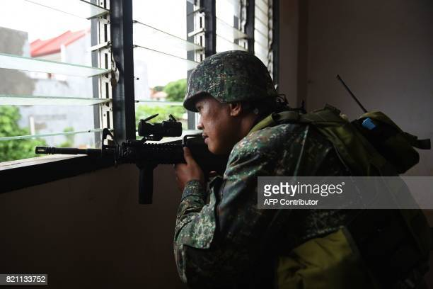 This photo taken on July 22 2017 shows a Philippine Marine observing Islamic militant positions on the frontline in Marawi on the southern island of...