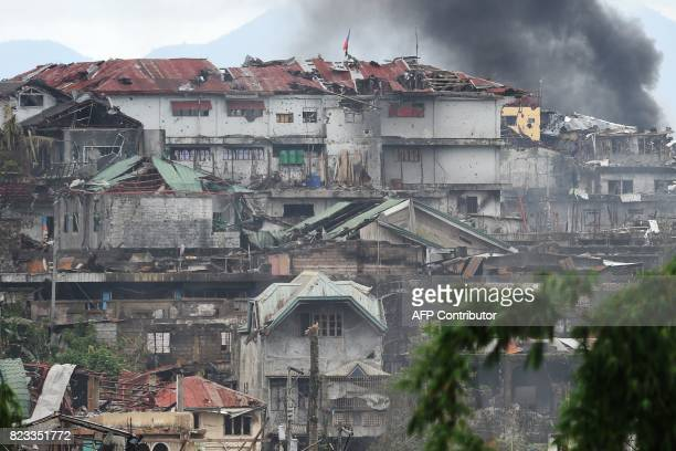 This photo taken on July 22 2017 shows black smoke billowing from a burning house after an an aerial strike by Philippine airforce attack helicopters...