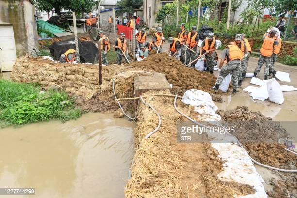 This photo taken on July 22, 2020 shows Chinese soldiers strengthening a levee with sandbags in preparation of floods from the Huaihe River in...