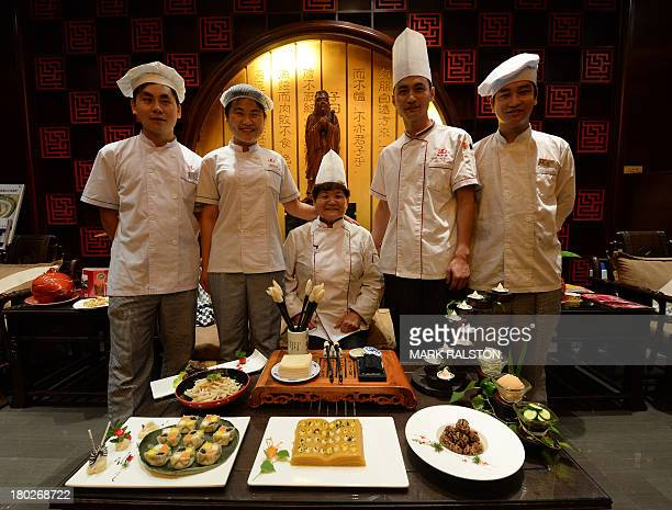 This photo taken on July 24 2013 shows chef Wang Xinglan with other chefs who specialize in Confucius cuisine with some of her dishes at a restaurant...