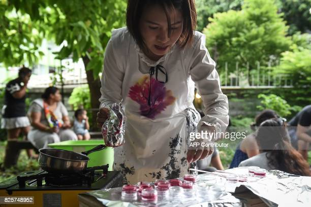 This photo taken on July 24 2017 shows Prontip Mankong a former political prisoner pouring melteddown lipstick into small containers to be given to...
