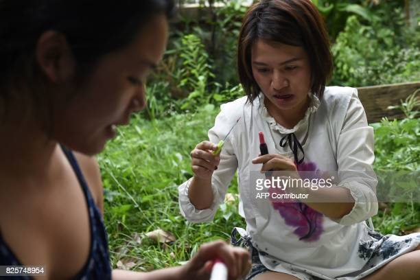 This photo taken on July 24 2017 shows Prontip Mankong a former political prisoner cutting the top off a donated tube of lipstick in Bangkok...