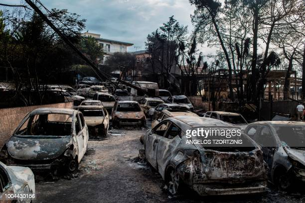 TOPSHOT This photo taken on July 24 2018 show cars burnt following a wildfire at the village of Mati near Athens on July 24 2018 Fifty people have...