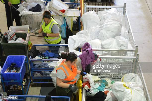 This photo taken on July 24 2018 shows workers sorting out clothing at the St Vincent de Paul Society a major charity recycling clothes in Sydney...