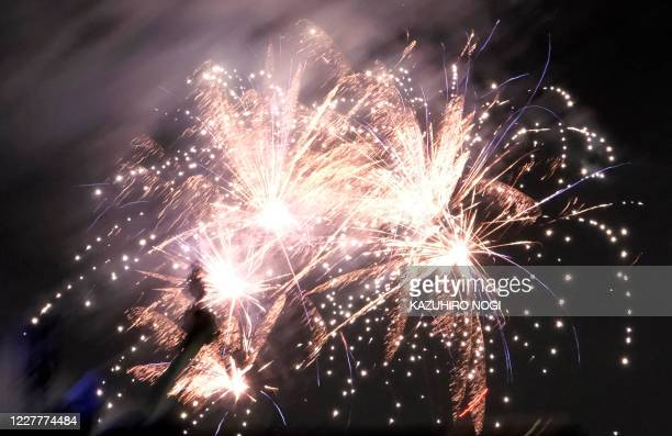 This photo taken on July 24, 2020 shows fireworks lighting up the night sky over Tokyo's Toshimaen amusement park during a summer fireworks festival,...