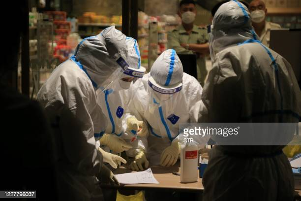 This photo taken on July 25, 2020 shows health workers carrying out COVID-19 coronavirus tests in a shopping mall in Dalian, in China's northeast...