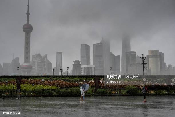 This photo taken on July 25, 2021 shows people posing for a photo along an empty Bund in Shanghai, as most people stay indoors due to wind and rain...