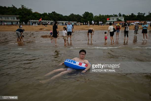 TOPSHOT This photo taken on July 26 2020 shows a man with a water float by the Second Bathing Beach in Qingdao east China's Shandong Province