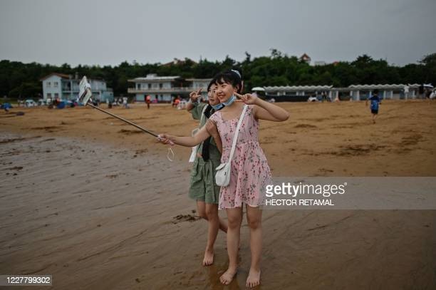 This photo taken on July 26 2020 shows a woman taking a selfie at the Second Bathing Beach in Qingdao east China's Shandong Province