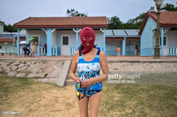 TOPSHOT This photo taken on July 26 2020 shows a woman wearing a facekini at the Second Bathing Beach in Qingdao east China's Shandong Province