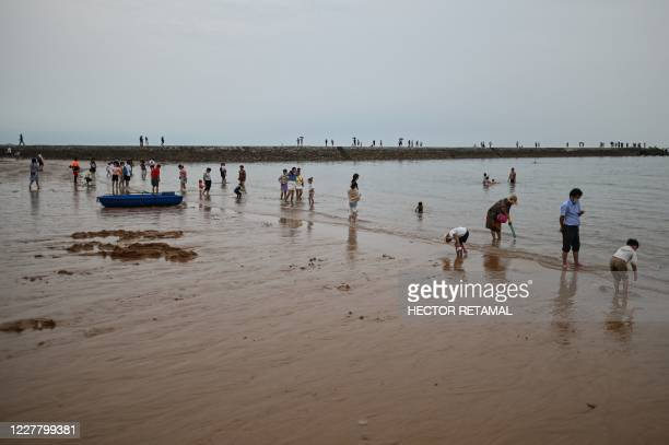 This photo taken on July 26 2020 shows people by the Second Bathing Beach in Qingdao east China's Shandong Province