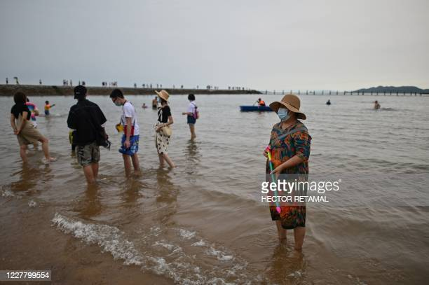 This photo taken on July 26 2020 shows people wearing face masks at the Second Bathing Beach in Qingdao east China's Shandong Province