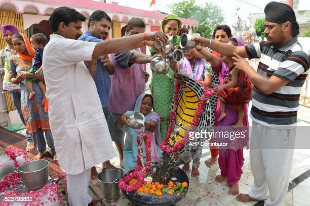 This photo taken on July 27 2017 shows Indian Hindu devotees pouring milk over an idol of a cobra snake during the Nag Panchami festival at a temple...