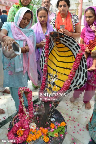 This photo taken on July 27 2017 shows Indian Hindu devotees pouring milk over a statue of a cobra snake during the Nag Panchami festival at a temple...