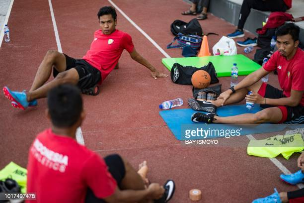 This photo taken on July 27 2018 shows Indonesian sprinter Lalu Zohri sitting with his teammates at the Senayan sport complex in Jakarta ahead of the...