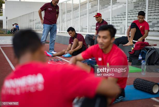 This photo taken on July 27 2018 shows Indonesian sprinter Lalu Zohri wearing his shoes at the Senayan sport complex in Jakarta ahead of the 2018...