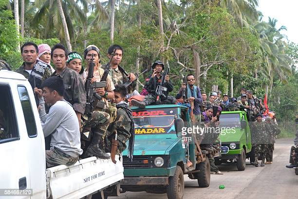 This photo taken on July 29 2016 shows hundreds of Muslim rebels from the Moro National Liberation Front aboard vehicles gather at a village as they...