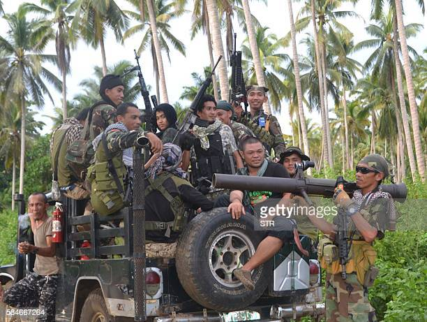 This photo taken on July 29 2016 shows Muslim rebels from the Moro National Liberation Front aboard a vehicle gathering at a village as they await...