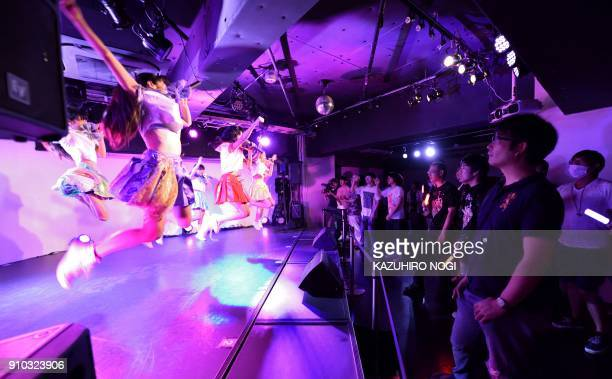 This photo taken on July 29 2017 shows adults watching a concert by an idol group in Tokyo Idol groups are common in Japan where rights groups have...