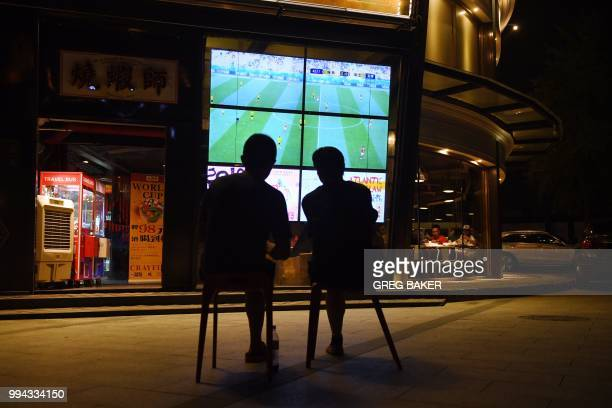 This photo taken on July 3, 2018 shows two football fans watching the 2018 Russia World Cup football match between Sweden and Switzerland on a TV...