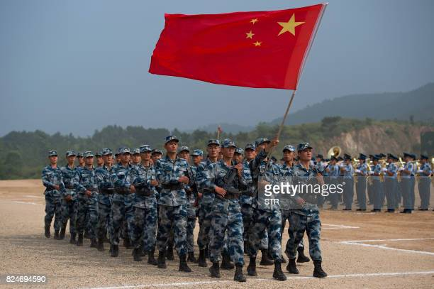 This photo taken on July 30 2017 shows Chinese People's Liberation Army Air Force personnel marching with their national flag during the opening...