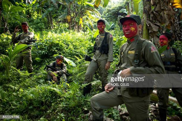 This photo taken on July 30, 2017 shows guerrillas of the New People's Army resting among bushes in the Sierra Madre mountain range, located east of...