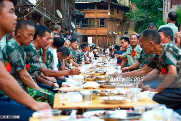 This photo taken on July 30 2017 shows soldiers and their families at a long table banquet hosted by people of the Dong ethnic minority which is a...